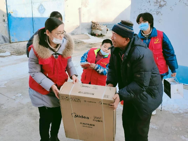 """志愿者为""""希望小屋""""捐赠取暖器。"""